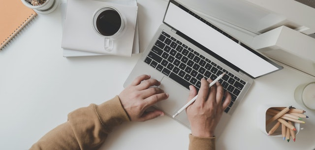 working man is typing on black frame laptop