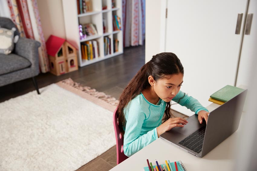 young girl sitting at desk in bedroom using AZYCUS